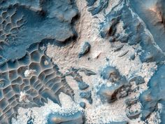 Bright material litters the floor of a trough in Noctis Labyrinthus, a maze-like region of deep valleys near one of Mars's volcanic plains.    Snapped by NASA's Mars Reconnaissance Orbiter, data from the spacecraft suggests that the material is hydrated—that is, it contains water in its atomic structure.    Scientists think the hydrated material could have formed long ago, either from subsurface water upwelling in the trough or from surface ice melting from the heat of nearby volcanic…