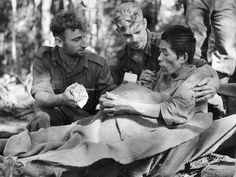 Australian stretcher bearers help a Japanese prisoner with malaria captured near Nauro in 1942.