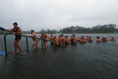 Members of Serpentine swimming club leave Serpentine river after their Christmas Day race during a heavy downpour in central London