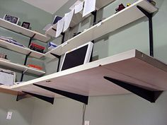 Use shelf standards and brackets for wall shelving and mount extra deep ones on the bottom for a hollow core door desk with no legs!
