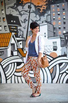 calça sequinha em laranja terroso com estampa pb de coelhos estilizados, regata azul marinho com listras brancas, blazer boyfriend branco de linho, sandália de tiras rasteira verde folha e telha, bolsa saco caramelo