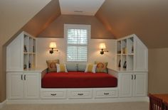 Family bonus room with slanted ceilings. Custom built ins and daybed create a great place to hang out with the kids and a comfortable space ...
