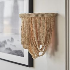 The Selita Sconce showcased by Palecek features tiny coco beads hand-sewn into draping ribbons, suspended from a powder-coated metal frame. This elegant sconce is exquisitely made and brings a soft coastal vibe to your home decor scheme. The Selita is the perfect wall light for hallways, entryways, or for either side of the fireplace mantle. Pair with the Selita Chandelier for a complete designer look.
