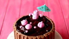 A rich, perfectly moist chocolate mud cake is made that much better with Kit Kats and piggies on top! Ingredients: Cake, 600g Kit Kats, 150g cocoa powder, 520g all-purpose flour, 1 tsp salt, 1 ½ tsp bicarbonate of soda, 675g caster sugar, 525g unsalted butter, softened, 6 large eggs, at room temperature, 3 tsp vanilla extract, 525ml milk, Simple syrup (see notes), Chocolate ganache, 600g dark cooking chocolate, 250g thickened cream, Piggy's, 400g pink fondant, skewer to decorate