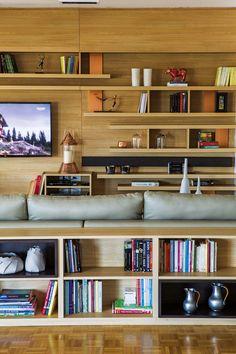Zona de TV y entretenimiento en un depto de Belgrano, con amplia biblioteca en melamina 'Roble natural' (Masisa) y espacio aprovechado como biblioteca alrededor del sillón.