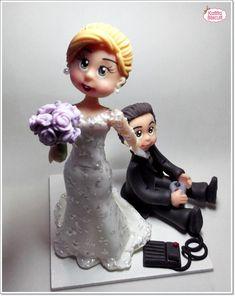 Noivinha puxando o noivo que está segurando um console de vídeo game pela gravata.  Fazemos personalizados com as características dos noivos. R$ 120,00