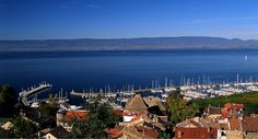 Port of Thonon-les-Bains looking toward Switzerland and the Jura mountains © Savoie Mont Blanc / Huchette (We had crossed the frontier, and were climbing now toward Thonon. Evian Les Bains, La Rive, Lake Geneva, Camping Car, San Francisco Skyline, Paris Skyline, Images, France, River
