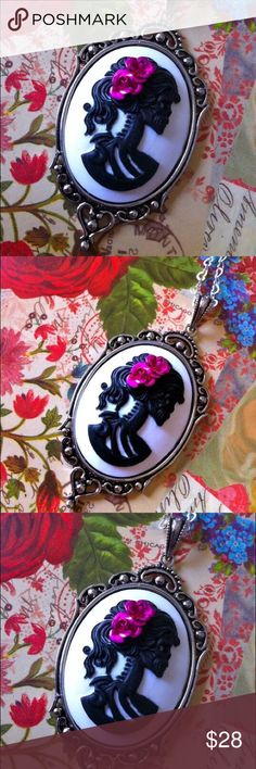 """Skull Necklace - Skeleton Lady Cameo Necklace This beautiful Skull Necklace features a Lady Skeleton detailed in black on a white background. Handmade and decorated with pink roses in her hair as a remembrance to the Day of the Dead holiday. Perfect for those who enjoy a bit of romance mixed with steampunk! Comes with an 18"""" Sterling Silver Plated Chain. Pendant is approximately 2"""" L. Couture by Lolita Jewelry Necklaces"""
