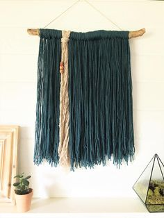This one-of-a-kind bohemian wall hanging features a piece of driftwood that I personally found at a beach or lake. Hanging from the driftwood is teal yarn with a small section of beige yarn with three wood beads tied on. Hang it on any wall or float it like a dream catcher in your