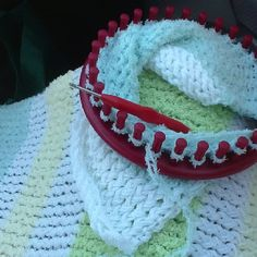 Baby blanket made with a round loom. A first for me. I usually crochet. I have the first strip made. I ended up creating three panels that I stitched together. Each strip is made on the loom, but the circle is not completed... it is knitted one direction, then back.
