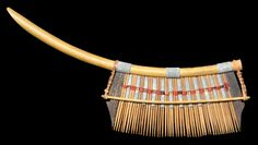 Fine Wood Stick Comb | Karo-Batak, Sumatra, Indonesia | 19th century. | This small comb is from the Karo-Batak people of northern Sumatra. It is a wood stick comb woven and bound to a thin, curved bamboo handle using red cotton thread, fibre and lead-coloured  strips.  | The Jen Cruse Collection  It was acquired in 1998 from a dealer in 'eastern' artifacts and was said to have been collected by a Captain L.M.Griffiths before 1868 on one of his voyages.