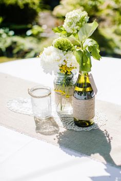 Centerpieces do not always have to be massive to have a big impact.  Love how this couple used simple burlap and wine bottles with a mix of natural flowers, for a classic touch DIY look. Photos by Clane Gessel Photography | #weddings #photography #flowers