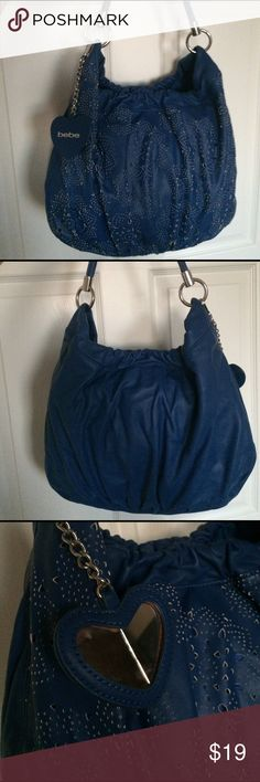 Bebe Blue Purse with Flower Perforated Front Dets Used but in good condition medium size faux leather Bebe purse. 1 handle with silver hardware. Magnet button closure. Interior features 2 smaller pockets and 1 larger zippered pocket. The heart charm has a cracked mirror! bebe Bags