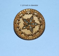 This is a gorgeous button.  A 5-point star of stamped brass sticks up through a perforated sheet of thin, dyed celluloid.  The star itself is decorated with imitation facetted steels of celluloid, which come through the pierced brass design.  It has a stamped, pierced, brass border, steel back and wire shank. The back shows wear and the front appears flawless.  The detail is beautiful.  Questions?  Please ask.  Thank you for viewing.  Shipping is free! | eBay!