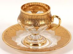 FOOTED GLASS CUP AND SAUCER. Footed glass cup and saucer with heavy gold encrusted decoration. Marked: 55/11. Size: cup: 3''H, 2 1/4''diam. top, 3''Diam. widest part.Saucer: 5 1/2''Diam. Condition: wear to gilt.