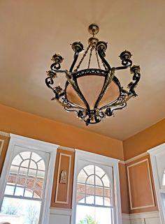 A chandelier in a corner of Bar Castaneda Corner, Chandelier, Ceiling Lights, Bar, Candelabra, Chandeliers, Outdoor Ceiling Lights, Candle Holders, Ceiling Fixtures