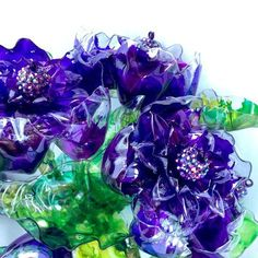 This unique purple bouquet of glass like flowers are made from discarded plastic water, soda and juice bottles that have been carefully cleaned, cut, hand painted and heat hardened. This particular bouquet is hand painted in various shades of plum, deep purple and violet. The leaves are painted in shades of emerald green, lime green and teal green. Although it is plastic it mimics the look of blown glass and is much more beautiful in person - these pictures do not show how truly beautiful it…