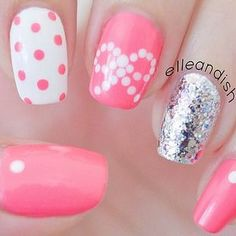 Estilosas uñas en rosa, blanco, plateado, algunas decoradas con lunares en color blanco y rosa, brillos plateados y el diseño de un lazo.