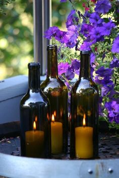 wine bottles with pillar candles.. hint * you cut the bottom off!