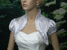 This is a white puff short sleeve bolero jacket made of bridal satin with ruffled edges. We also have other colors available. This item is newly made and ready to ship.  We have Small, Medium, Large and X-Large size that you can choose from. Small size normally fits US size 0-4 Medium size normally fits US size 6-8 Large size normally fits US size 10-12; X-Large size normally fits US size 14-16 Measurements:  OUR SIZE Small Medium Large X-Large Back Length 12 13 13.5 14 Shoulder 15 16 17 18…
