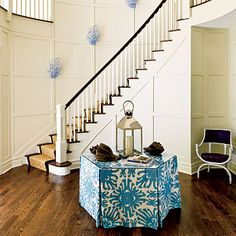 coral-shaped sconces with periwinkle paint & a hexagonal table covered in a blue-and-white-print fabric.
