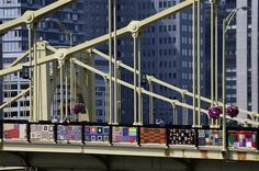 Yarn Bomb - Pedestrians walk across the Andy Warhol bridge on Monday, Aug. 12, 2013 in downtown Pittsburgh. More that 1,800 knitters have covered the bridge in 3,000 feet of colorful yarn. Volunteers worked all weekend to attach 580 blanket-sized, hand- knitted panels to the pedestrian walkways. Organizers say it is the nation's largest yarn bomb.