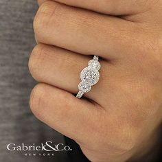 Gabriel NY - Preferred Fine Jewelry and Bridal Brand. 14k White/Rose Gold Round 3 Stones Halo  Engagement Ring. This sparkling three stone engagement ring with a diamond band also features surprise rose gold details. Find your nearest retailer-> https://www.gabrielny.com/storelocator