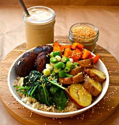 A Roasted Garlic Buddha Bowl bursting with nutty brown rice, sweet roasted vegetables,wilted greens, crunchy raw green onions, sesame seeds & heavenly roasted garlic sauce.