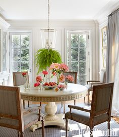 """The breakfast room is definitely a morning room,"""" Smith says. It's light and airy, with pale gray Regency armchairs by Noir gathered around Hickory Chair's Gustav table. Zurich lantern by Vaughan. William Abranowicz  - HouseBeautiful.com"""