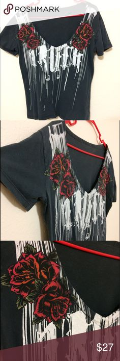 Black v-neck T-shirt with roses This black v-neck low cut T-shirt is one of a kind! There are roses on both shoulders that have a mixture of bright orange and red colors. Almost looks like a tattoo. The white part is hard to read but it says TRUTH across the whole front. There is fading all along the the trim as seen in the pictures but it fits in. There is no tag anymore, it was printed on the shirt but has faded off. This shirt was purchased from an NOTW store. This has the perfect metal…