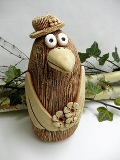 Ptáček+s+kloboukem+a+kyticí+Ze+šamotové+hlíny,+vhodné+i+k+venkovní+dekoraci.+Výška+23+cm.