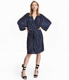 Dark blue. Knee-length dress in pleated, woven fabric with a sheen. Low-cut V-neck and wrapover detail at front, 3/4-length dolman sleeves, elasticized seam