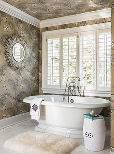 Elegant master bath with classic subtly-patterned floral print wallpaper and a freestanding tub.