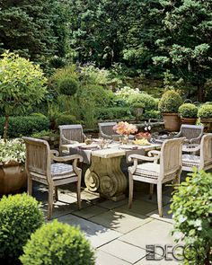 A marble-top table by Michael Trapp amid boxwood and a koi pond in the garden.