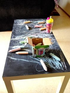 pick up an old coffee table and paint with chalkboard paint. You can also buy whiteboard paint