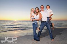 Family on the beach...cute pose. Hate that they all match, though.