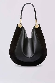 This modern hobo bag is made in a soft leather and suede, and accented with sleek gold hardware. It has a leather strap and magnetic snap closure.
