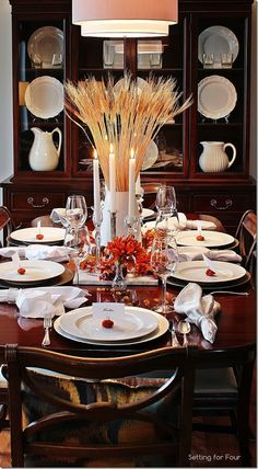I love the large wheat sheaf centerpiece and pops of orange with the white dishes in this Thanksgiving tablescape!