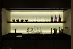 Kitchen shelving display with backlit glass splashback using Contour LED strip lights - http://www.johncullenlighting.co.uk/products/shelf-and-cove-lights/contour/