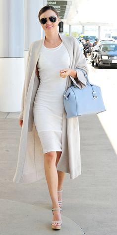 Miranda Kerr in a long cardigan, white dress, and wedge sandals