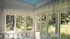 Summer glass veranda with hand made lace curtains.