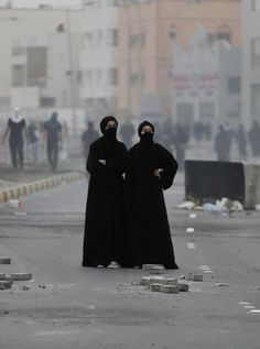 Bahraini anti-government protesters standing in tear gas and smoke from burning debris look toward police positions during clashes. Protesters took to the streets in predominantly Shiite areas of Bahrain and set tires alight along a major highway to mark the fourth anniversary of widespread protests calling for reform in the island nation, February 14, 2015 -- at Al Daih, Bahrain.  Photo credit: AP Photo / Hasan Jamali