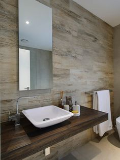 This sleek modern bathroom gives the feel of a spa or bathhouse somewhere far away. #staycation The stone looks gorgeous against the streamlined wood vanity shelf.