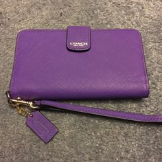 Coach wristlet Purple saffiano wristlet. Will fit an iPhone 6 with thin or no case. Used once! Beautiful! Measures 6 x 1 x 3.5 Coach Bags Clutches & Wristlets