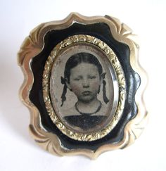 Antique Victorian Mourning Photo Pin Brooch, Little Girl Wednesday Addams Look-a-like, Gilt & Enamel Frame, Post Mort. $245.00, via Etsy.