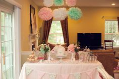 elegant beautiful pink and teal first birthday party for twin girls dessert table with bunting banner and tissue poms