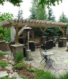 As #LandscapeDesigners in Minneapolis MN, we try to adapt our ideas for use in many seasons.  The pergola over this flagstone patio gives shade in summer, and the portable heater warms things up on cool nights.  The stone of the fireplace is repeated in the pillar bases as well as the counter and grill area.  And the patio has lots of different seating areas.  http://www.aldmn.com
