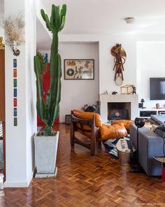 A decoração dessa sala de estar aconchegante conta com objetos inusitados como cactus, arte nas paredes e a famosa poltrona mole.