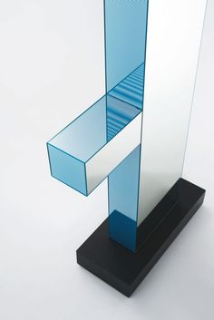 SHIBAM 1 design Ettore Sottsass   Totem mirror with object holder shelf. The two frontal sides are in white mirror and the lateral ones in decorated mirror with thin coloured engravings (available in the colours pink and light blue). The base is in matt polished absolute black granite.