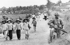 In this December 1965 photo, a U.S. 1st Division soldier guards Route 7 as Vietnamese women and school children return home to the village of Xuan Dien from Ben Cat, Vietnam.